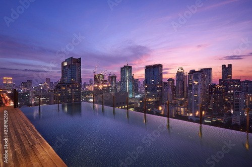 Foto op Aluminium Buffel Cityscape sunset view of Bangkok modern office business building and high skyscraper in business district with infinity view swimming pool at Bangkok,Thailand.