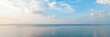 Bright beautiful seascape, sandy beach, clouds reflected in the water, natural minimalistic background and texture, panoramic view banner