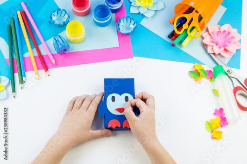 Fotografie, Obraz  Child hands making a penguin out of paper