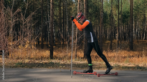 Training an athlete on the roller skaters. Biathlon ride on the roller skis with ski poles, in the helmet. Autumn workout. Roller sport. Adult man riding on skates. Athlete is getting ready to start.