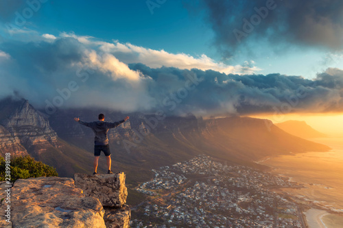 Cuadros en Lienzo Young man standing on the edge at the top of Lion's head mountain in Cape Town w