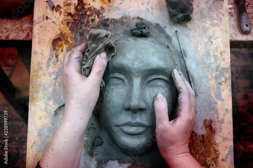 The hands of the sculptor mold the clay mask Fototapet