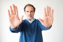 Serious Handsome Middle Aged Man Making Stop Gesture. Mature Man Gesturing Forbidden With Two Hands. Isolated On White. Prohibition Concept