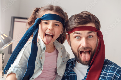 Fotografie, Obraz Father and little daughter at home sitting wearing ties tongue out grimace