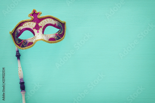 Poster Carnaval carnival party celebration concept with elegant purple mask on stick over mint wooden background. Top view.
