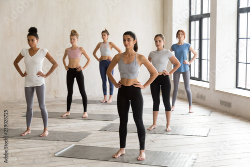 Fényképezés  Five multiracial slim females wearing sportswear standing in rows barefoot on rubber black mats ready to start workout at fitness centre