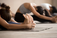 Females Wearing Sportswear Doing Exercise Stretching Full Body Reducing Anxiety And Fatigue, Paschimottanasana Seated Forward Bend Pose, Close Up Focus On Girl Feet And Arms. Group Training Concept