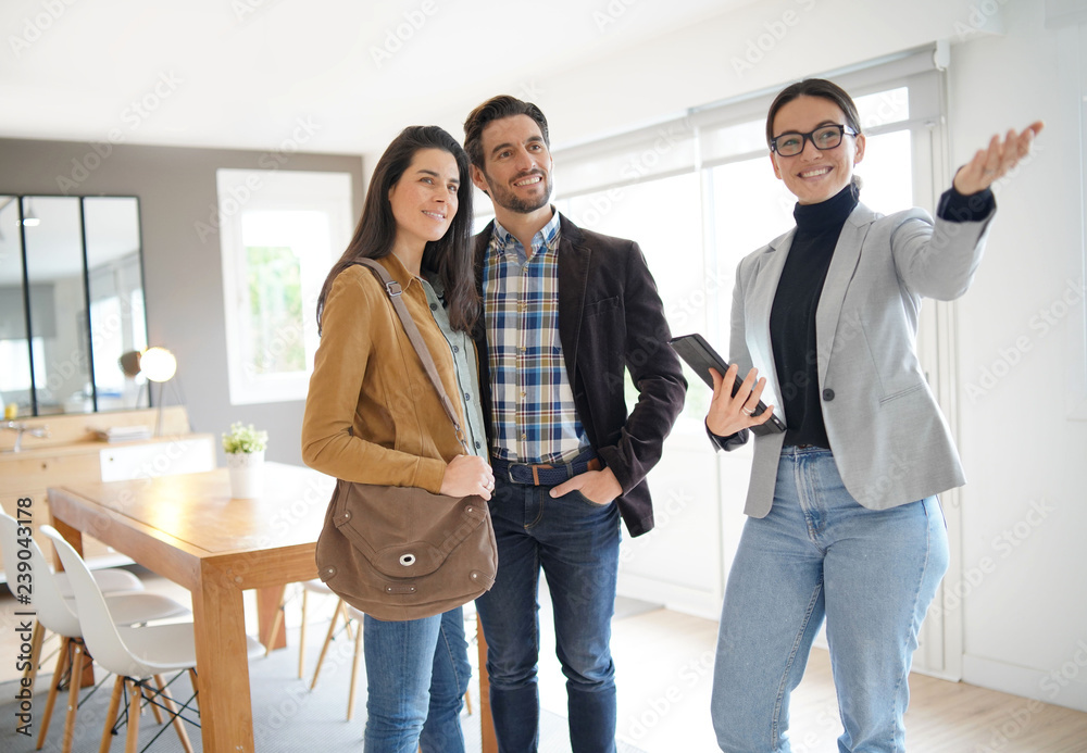 Fototapeta Real estate agent showing modern house to attractive couple