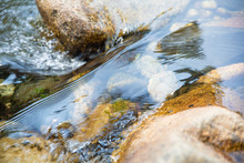 Close Up Detail Of Beautiful Brilliant And Transparent Water Flowing On Rocks And Stones In River