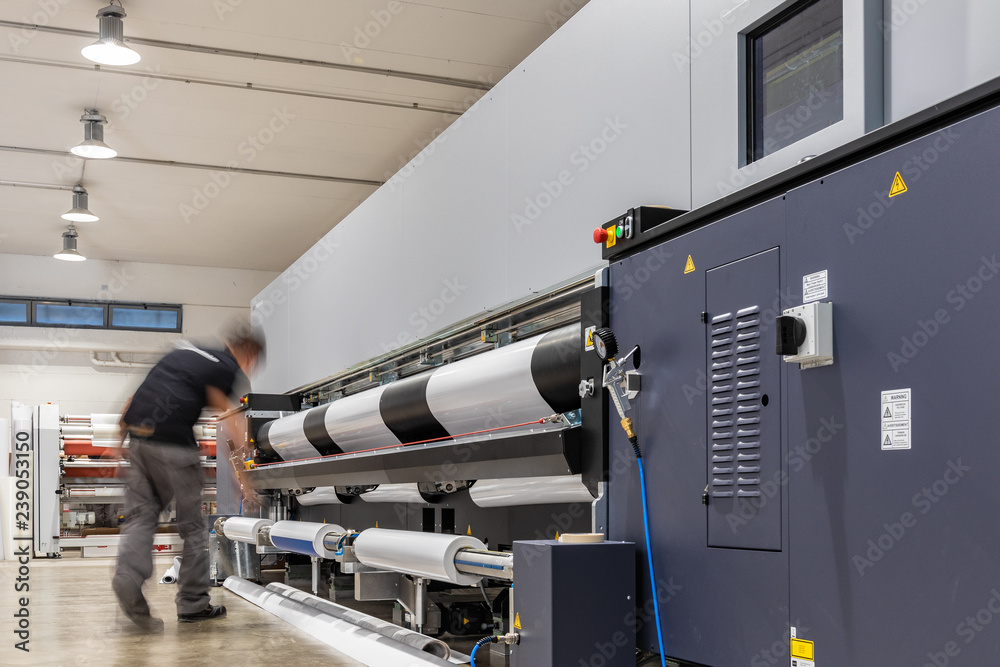 Fototapeta Big paper feed during Computer aided printing process, advanced technology in the press and publishing sector, latest generation robotized plotting machines for mass production and big format prints.
