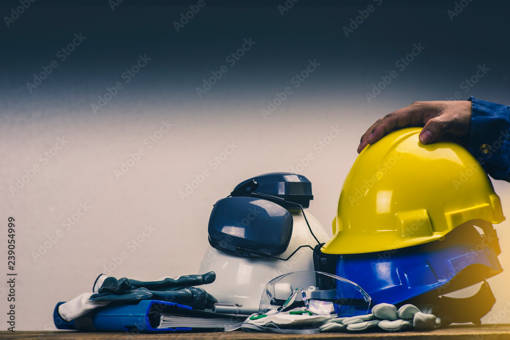 Fototapeta Works safety concept: PPE (Personal Protective Equipment), hard hat or industrial helmet for protection the worker from accident during working at construction site, factory or industry building.