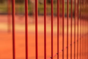 lawn field for playing basketball behind the orange fence mesh. Metal mesh wire fence with tennis court.