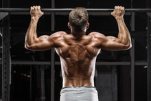 Muscular Man Doing Pull Up On Horizontal Bar In Gym, Working Out. Strong Fitness Male Pulling Up, Showing Back, Outdoors