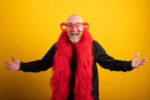 Bald Man Having Fun Wearing Vibrant Red Feather Boa And Heart Shaped Glasses