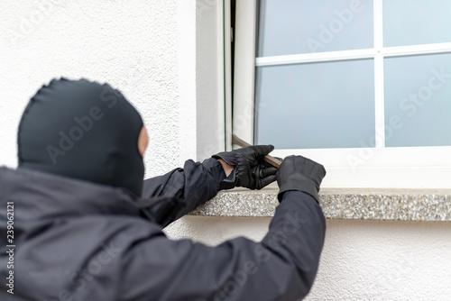 Valokuvatapetti Einbrecher will mit einer Brechstange eine Haustür aufhebeln