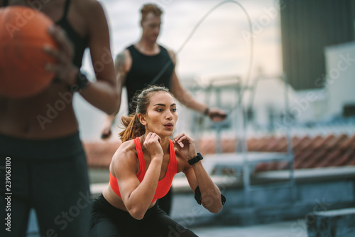 Slika na platnu Fitness man and women training on rooftop
