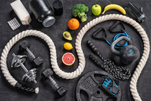 Sports Equipment And Healthy Nutrition On A Black Background. Top View. Motivation