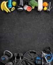 Sports Equipment And Organic Food On A Black Background. Top View. Motivation