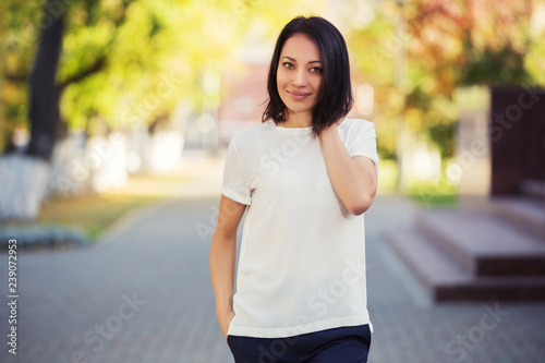 Happy young fashion woman in white t-shirt on city street Canvas