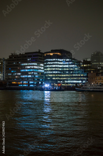 Fotografie, Obraz  Offices on the bank of river thames and illuminated with lights having reflectio