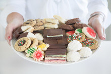 Christmas Photograph Of A Woman's Hands Holding A Platter Of Homemade Christmas Cookies On White