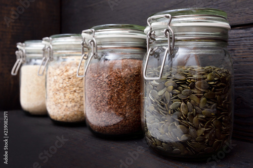 Various seeds in storage jars in pantry, dark wooden background. Smart kitchen organization