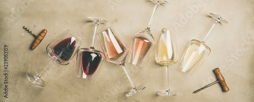 Fotografie, Obraz Flat-lay of red, rose and white wine in glasses and corkscrews over grey concrete background, top view, wide composition