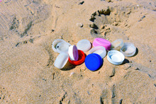 Colored Plastic Caps Abandoned On The Beach