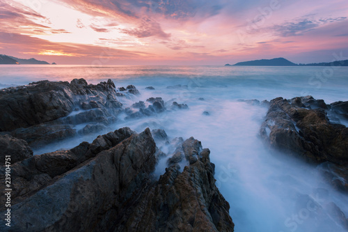 Fényképezés  Long exposure image of Dramatic sky and wave seascape with rock in sunset scenery background
