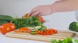A woman in the kitchen cuts fresh vegetables and puts them in a plate, prepares a delicious salad for lunch