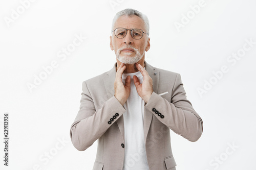 Old man feeling discomfort in throat standing gloomy and unhappy being unable gi Wallpaper Mural