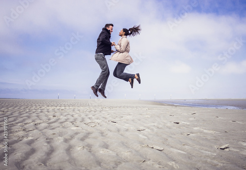 Photo Happy young couple jumping in the air together at the beach of Skt