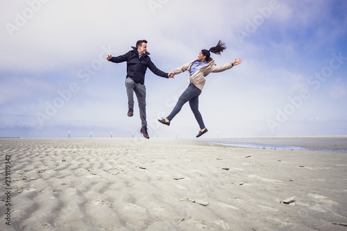 Photo Happy young couple jumping in the air at a northern sea beach in Germany