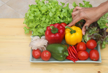 Closeup of woman's hand catching organic fresh vegetables in ceramic plate on wooden table. Preparation for healthy food cooking.