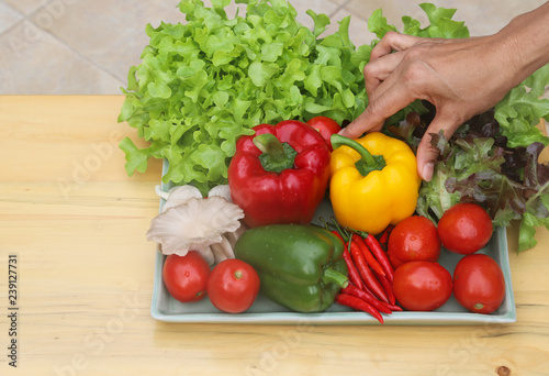 Canvas Prints Fresh vegetables Closeup of woman's hand catching organic fresh vegetables in ceramic plate on wooden table. Preparation for healthy food cooking.