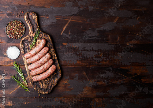 Raw beef and pork sausage on vintage chopping board with salt and pepper on dark wooden background.