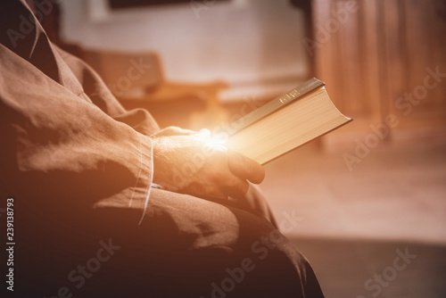 Fotografia A monk in robes with holy bible in their hands praying in the church