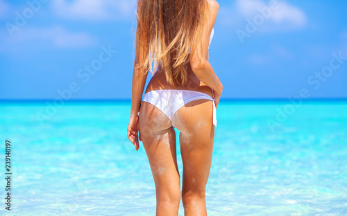 Obraz Travel vacation wallpaper - Beautiful young pretty blonde girl in white bikini with white sand on her perfect sport sexy body relax in sea of white sand paradise tropical maldives beach at sunny day - fototapety do salonu