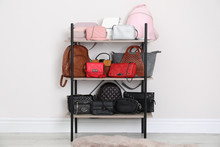 Shelving Unit With Stylish Purses Near White Wall. Element Of Dressing Room Interior