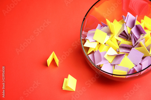 Obraz Paper pieces for lottery in glass vase on color background. Space for text - fototapety do salonu