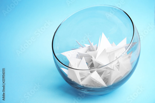 Obraz Paper pieces for lottery in glass vase on color background - fototapety do salonu