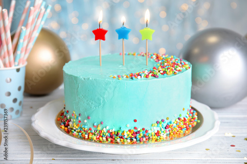 Fresh delicious birthday cake with candles on wooden table