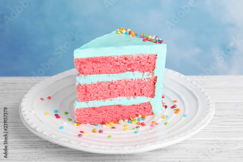 Slice of fresh delicious birthday cake on table against color background