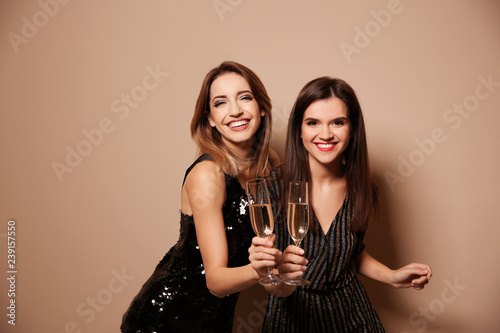 Beautiful women with glasses of champagne on color background