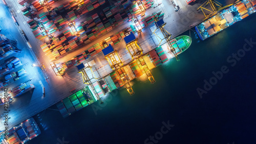 Valokuva Aerial top view container ship at sea port and working crane bridge loading container for import export, shipping or transportation concept background