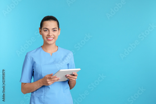 Obraz Portrait of young medical assistant with tablet on color background. Space for text - fototapety do salonu