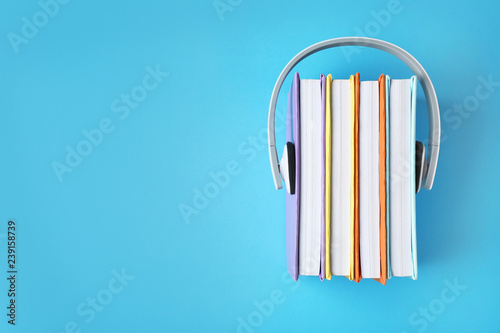 Valokuva  Modern headphones with hardcover books on color background, top view