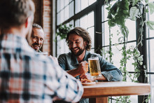 Cheerful Friends With Drinks Spending Time At Pub