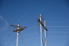 Electrical Utility Poles And High Voltage Power Lines, Electrical Grid Infrastructure, With A Blue Cloudless Sky In Wyoming, USA