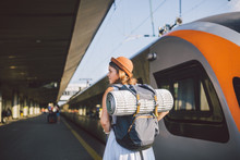 Theme Transportation And Travel. Young Caucasian Woman Standing At Train Station Platform Near Train Backs Train Background With Backpack Travel Mat Sleepy Weather In Dress And Hat In Summer